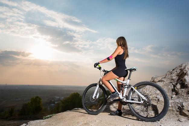 夕暮れ時の崖の上のマウンテンバイクの女性サイクリスト Premium写真