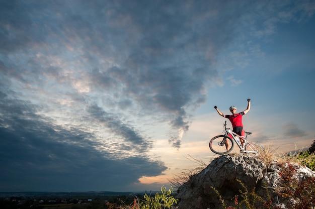 Велосипедист по пересеченной местности отдыхает на вершине горы Premium Фотографии