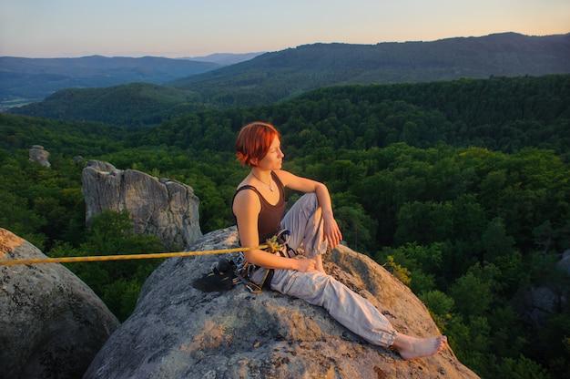 Девушка альпинист на вершине горы на большой высоте в вечернее время Premium Фотографии