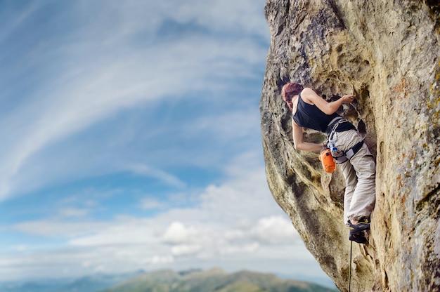 急な張り出した岩崖の上の女性ロック・クライマー Premium写真
