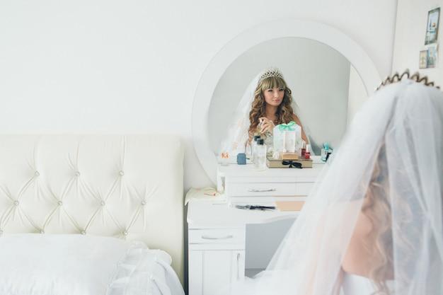 花嫁は鏡を見て、白い部屋で香水を使います Premium写真