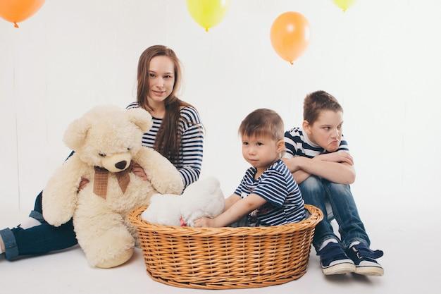 休日、楽しい家族のパーティー。色付きのボールの中で白い背景に大きなテディベアとバスケットの子供たちが誕生日を祝う Premium写真