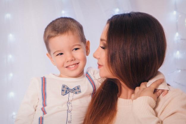 ライトと装飾的な要素の背景に彼の母の腕の中で子 Premium写真