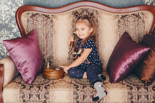 Маленькая девочка сидит на диване и разговаривает по старому телефону Premium Фотографии