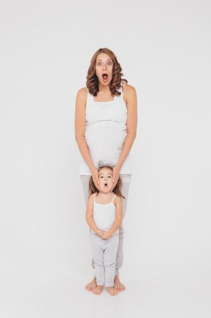 妊娠中の女性とスポーツウェアの少女 Premium写真