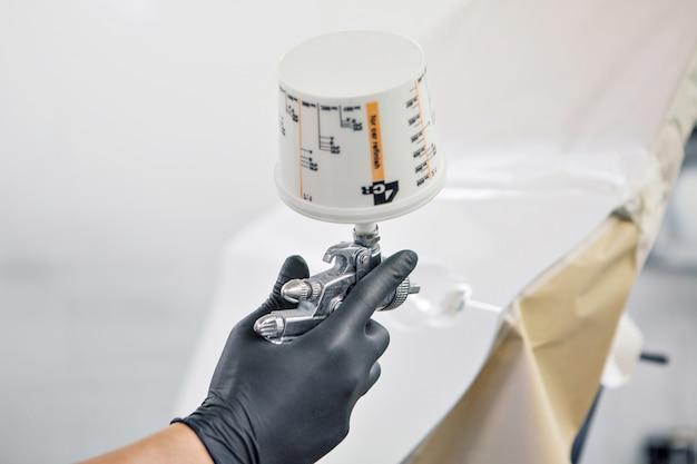 マシンのクローズアップの詳細。塗料は機械の表面に塗布されます Premium写真