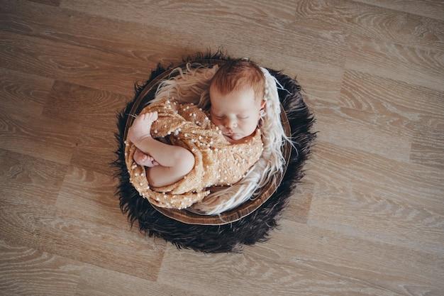 バスケットで寝ている毛布に包まれた生まれたばかりの赤ちゃん。小児期、医療、体外受精の概念。白黒写真 Premium写真