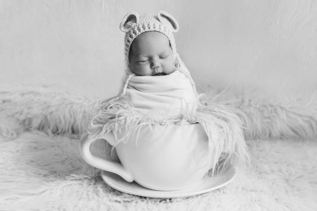 Новорожденный в большой чайной чашке. концепция детства, здоровье, эко, горячие напитки, завтрак Premium Фотографии