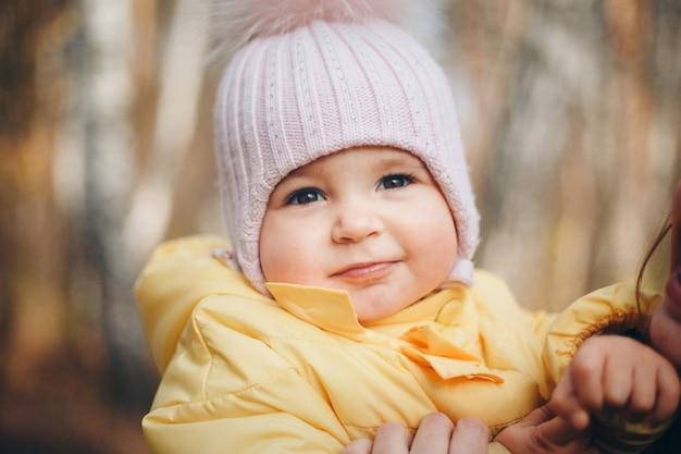 Маленькая девочка в теплой шапке на голове улыбнулась. концепция детства, здоровья, эко, холодного времени Premium Фотографии