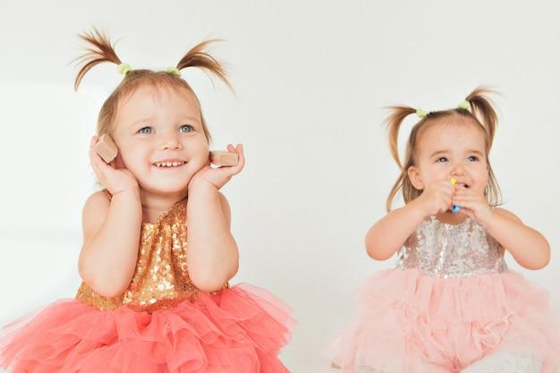 白い背景の上の床で遊ぶ二人の少女 Premium写真