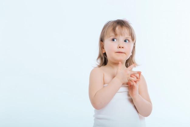 しかめっ面の少女。子供は何かをしている。感情、表情、子供時代、誠実さの概念 Premium写真