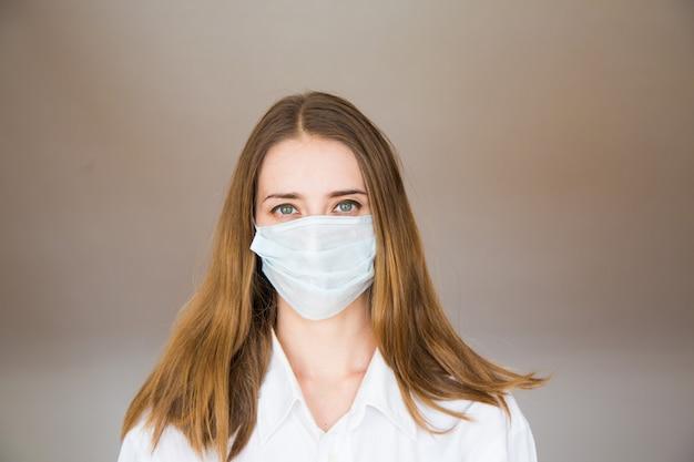 Портрет женщины на бежевом, который носит медицинскую маску. демонстрация медицинского оборудования. Premium Фотографии