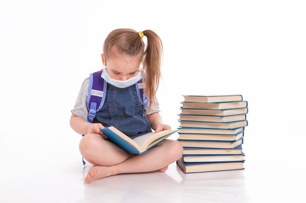 一年生は読むことを学ぶ。家庭用遠隔学習の小さな女の子。医療用マスクをした子供が本を読みます。 Premium写真