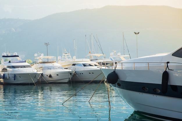 ボートポートと太陽の下で山の背景にヨットします。 Premium写真