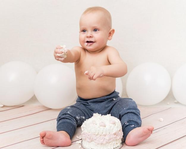 誕生日ケーキを食べる赤ちゃん Premium写真