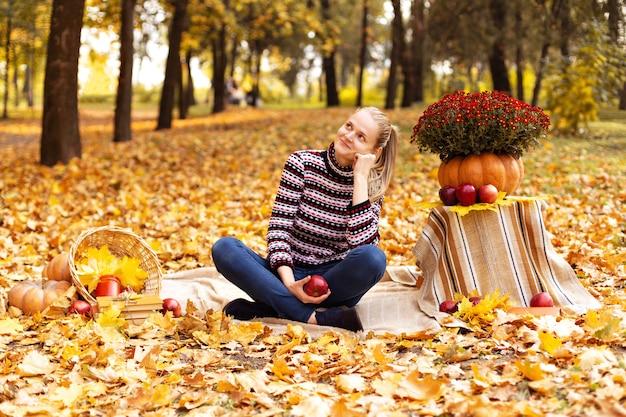 カエデの葉のある公園でのピクニックに若い女性の夢 Premium写真
