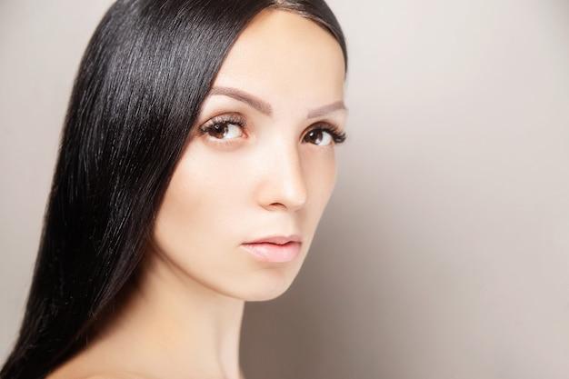 暗い光沢のある髪と長い茶色のまつげを持つ女性。女性の美しさの肖像画。まつげエクステンション、スキンケア、美容、スパのコンセプト Premium写真