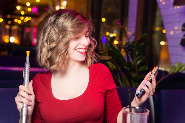 赤いドレスを着た若い女性は、水ギセルバーで水ギセルを吸うし、友人とチャットします。 Premium写真