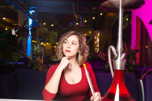 赤いドレスの若い女性は、水ギセルバーで水ギセルを吸います。 Premium写真