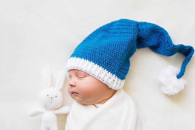 Новорожденный мальчик спит в рождественской шапке с вязаным кроликом на белом фоне Premium Фотографии