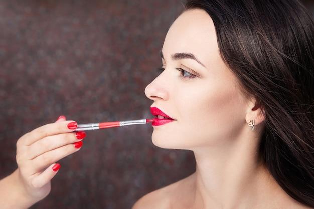 Визажист делает макияж красивой молодой женщине Premium Фотографии