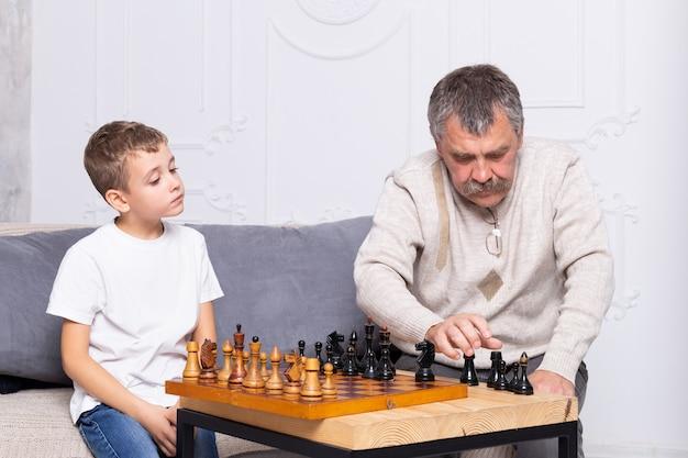 祖父は孫と屋内でチェスをしています。少年とおじいちゃんはリビングのソファーに座って遊んでいます Premium写真
