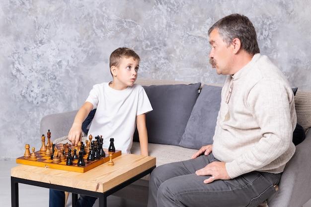 祖父は孫と屋内でチェスをしています。少年とおじいちゃんは、リビングルームのソファに座って、一緒に話している Premium写真