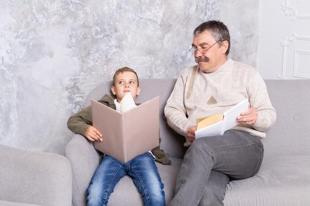 祖父と孫は、リビングルームで一緒に本を読んで座っています。少年と彼の笑顔のおじいちゃんは、屋内で一緒に時間を過ごします。子供を持つ年配の男性 Premium写真