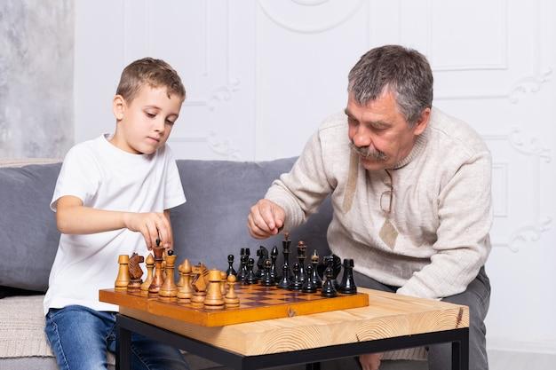 祖父は孫と屋内で古いチェスをしています。少年と彼のおじいちゃんは、リビングルームのソファに座って遊んでいます。年配の男性は子供にチェスをすることを教える Premium写真