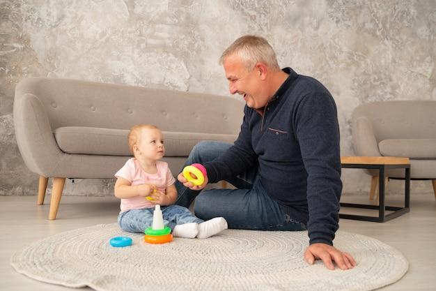 小さな女の赤ちゃんは、リビングルームで祖父母とピラミッドを収集します。祖父はソファの近くの床で孫娘と遊ぶ Premium写真