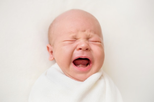 白い背景の上の生まれたばかりの赤ちゃんの男の子。赤ちゃんが泣いている Premium写真