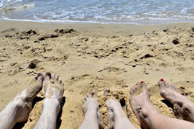 砂の上に横たわっている人々の足 Premium写真
