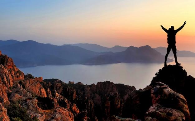 日没時の崖の上で楽しんでいるハイカーのシルエット Premium写真