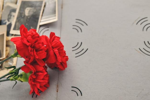 軍用写真の古いフォトアルバムの背景に赤いカーネーション。記憶と軍事的栄光の日。 Premium写真