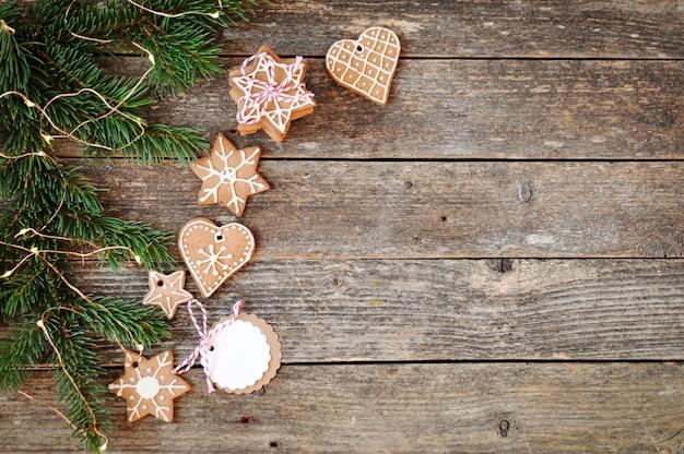 木製の伝統的な自家製クリスマスジンジャーブレッド砂糖フロスティングとギフトボックス。 Premium写真