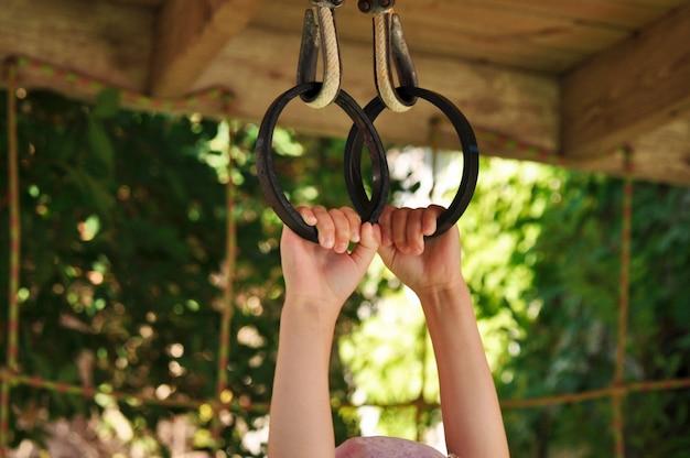 遊び場で金属リングにつかまって子供の手 Premium写真