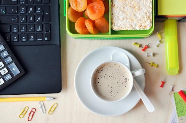 オフィスや学校での食べ物。デスクトップ上の健康食品と一杯のコーヒーのお弁当。上面図。 Premium写真