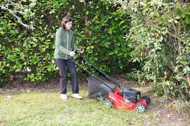 女性は彼女の庭の木の間の芝生を刈る Premium写真