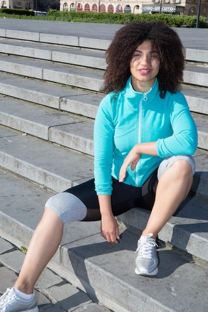 Молодая девушка сидит на улице после пробежки Premium Фотографии