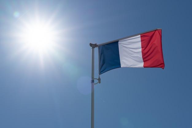 青い空と大きな太陽に手を振るフランスの旗 Premium写真