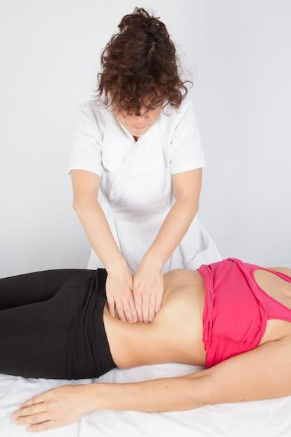 スパサロンで腹筋マッサージを受ける女性 Premium写真