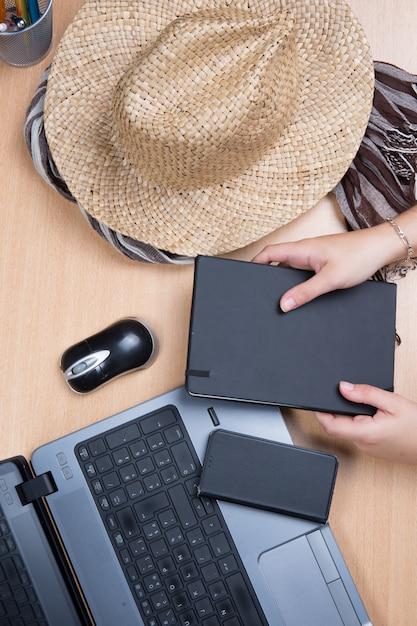 Руки держат ноутбук с ноутбуком и шляпу Premium Фотографии