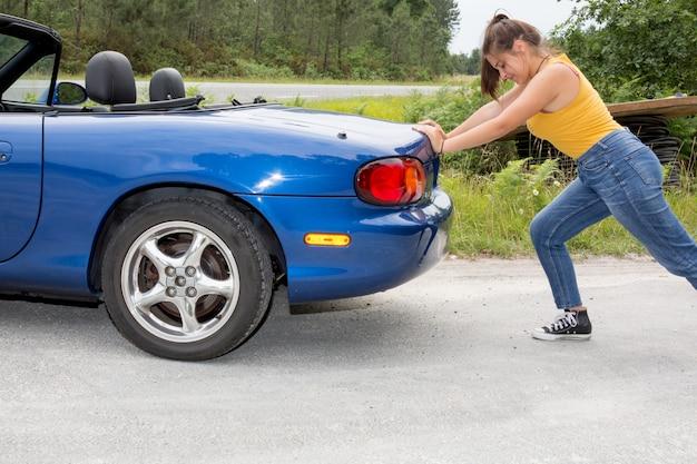 女性が車を押します。横で折れた Premium写真
