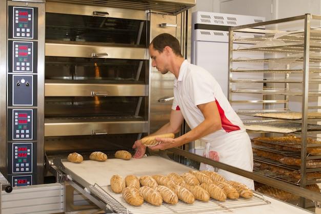 朝はパン屋に立って、パンを焼くパン屋 Premium写真