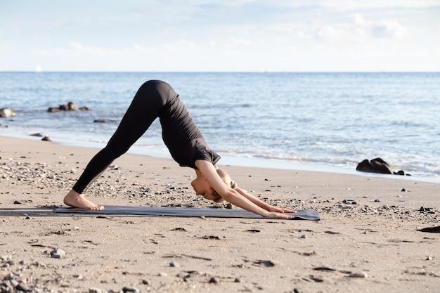 アジアの砂のビーチでヨガをやっている黒の若い女性 Premium写真