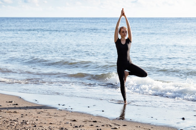砂のビーチでヨガをやっている黒の若い女性 Premium写真