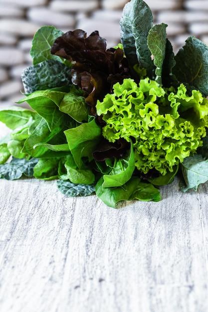 緑と赤のレタス、ケール、ほうれん草、石の背景と白いテーブルの上のアマランスの葉 Premium写真
