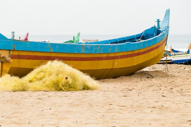 曇りの日にビーチでカラフルなボートやネットを釣りします。 Premium写真