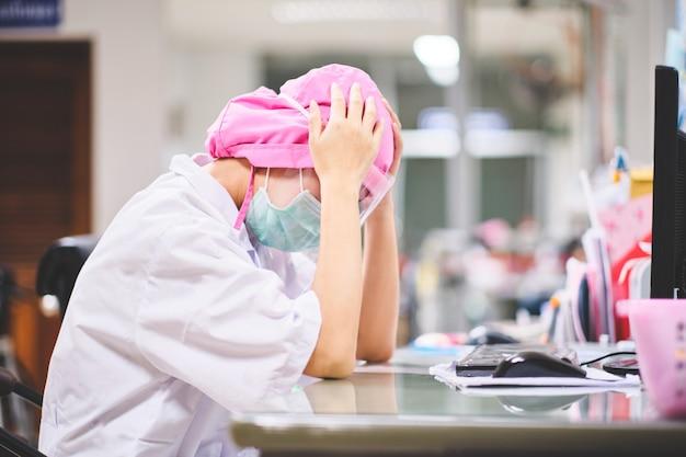 コンピューターの前で一生懸命働いてストレスや頭痛の下で女医 Premium写真
