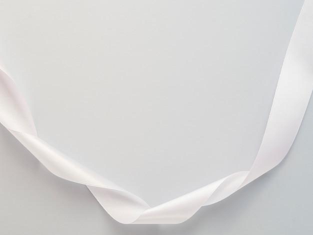 Пастельная сладкая белая атласная бант лента на белом фоне. Premium Фотографии
